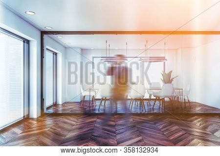 Blurry Young Businessman Walking Past Modern Conference Room With White And Glass Walls, Dark Wooden
