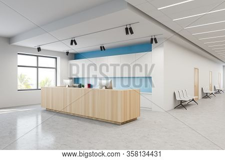 Corner Of Modern Hospital Corridor With White And Blue Walls, Concrete Floor And Wooden Reception De