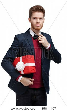 Young man  carries a present wrapped in red paper to someone, isolated on white