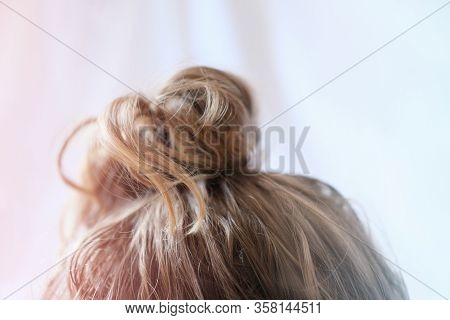 Messy Bun On The Head Of A Blonde Woman. Quick Hairdo At Home Because Of Quarantine. Modern Fast Hai