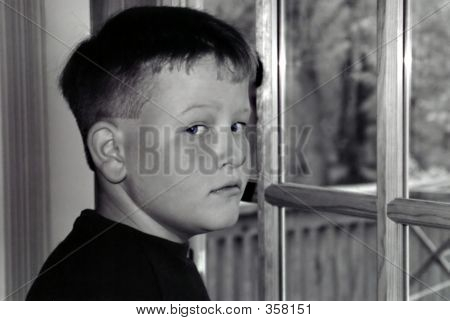 black & white portrait of a young boy caught daydreaming out his back door. ** Note: Slight blurriness, best at smaller sizes poster