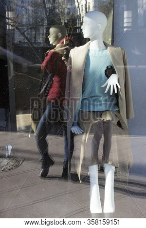 Reflection In A Shop Window Of A Womens Clothing Store. Mannequin Man Photographer Is Visible With A