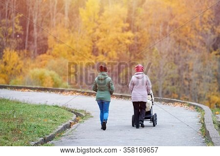 Grandmother And Daughter Walking In Autumn Park With Baby In Stroller, Back View. Single Parent. Clo