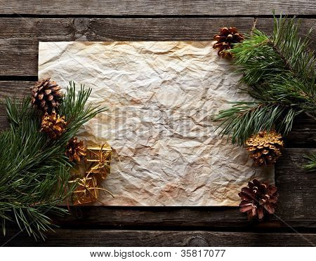 Old crumpled paper with spruce twigs and pinecones on old wood. Sweet Xmas holiday background.