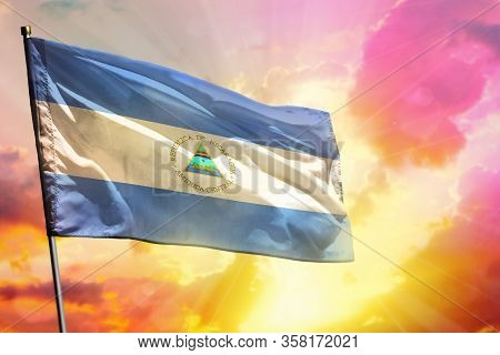Fluttering Nicaragua Flag On Beautiful Colorful Sunset Or Sunrise Background. Nicaragua Success And