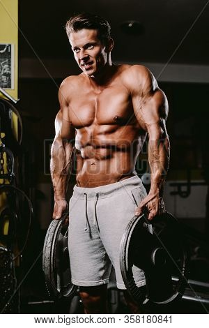 Muscular Fit Man Workout And Pumping Muscles.