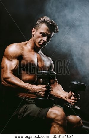Brutal Strong Bodybuilder Man Pumping Up Muscles In Gym