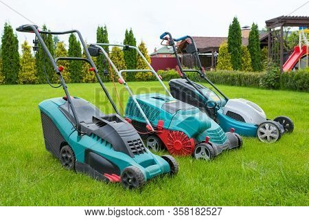 . Lawn Mowers Are Standing On The Lawn In The Garden Backyard. A Close-up Of An Electric Lawn Mower.