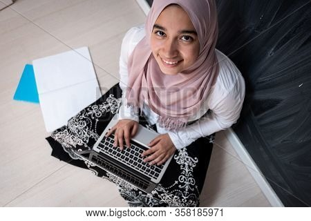 Muslim female student with laptop in classroom