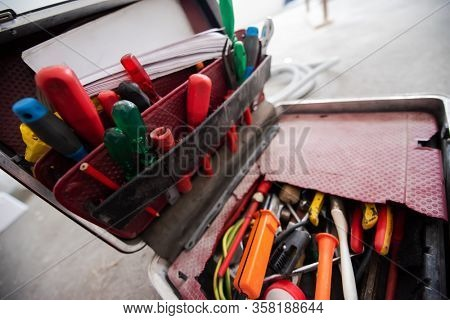 toolbox full of hand tools on real dusty floor background at construction site