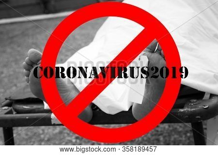 Coronavirus19. COVID-19. Coronavirus19 Dead Body, with an identification tag - blank sign attached to a toe. Covered with a white sheet. Dead Human due to COVID-19 Infection. International NO Symbol.