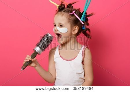 Close Up Portrait Of Pretty Little Girl Singing Her Favourite Song Into Hairbrush Isolated Over Pink