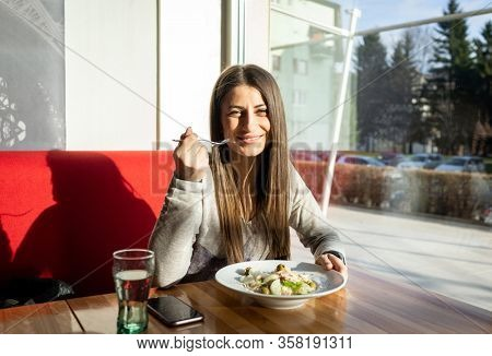 Young woman eating food in a restaurant, having lunch break
