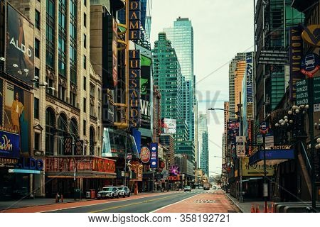 NEW YORK, USA - MARCH 21, 2020: Empty 42nd street with few pedestrians and traffic as the result of COVID-19 coronavirus pandemic outbreak in New York City.
