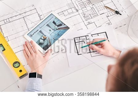 Above view of architect using digital tablet and blueprints while working on floor plan of flat