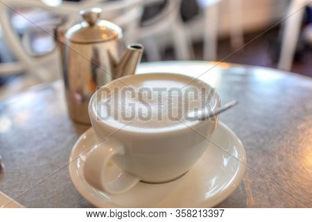 Focus On Hot London Fog Tea Latte Drink With Foamed Milk On Breakfast Table With Teapot In Backgroun