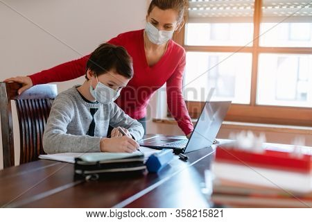 Mother and child having e-learning session with teacher during crisis doing homework