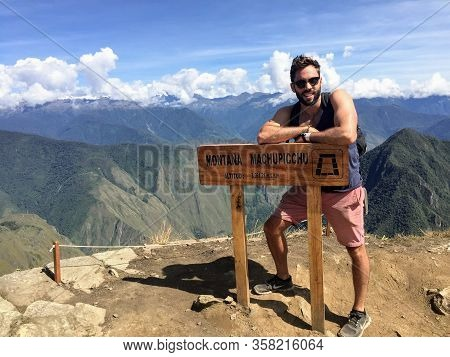 Machu Picchu Mountain - May 10th, 2016: A Young Male Tourist Standing Beside The Sign For The Summit