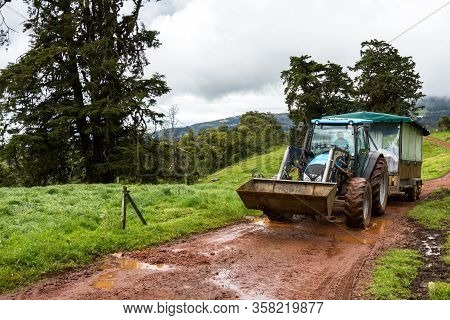 Alajuela, Costa Rica - January 20 2020: Tractor Riding On A Muddy Road With A Trailer For Tourists V