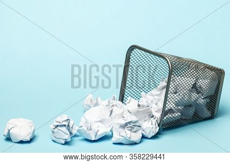 Overturned Trash Can With Crumpled Paper Balls On A Blue Background. Closeup Copy Space.