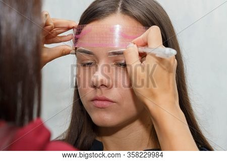 The Master Checks The Contour Of The Eyebrows Of The Client Before The Procedure With A Special Rule
