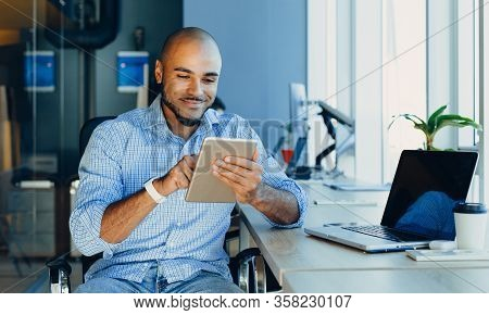 Handsome Cheerful African American Man In Creative Atmosphere Using Laptop Sitting On A Wooden Table