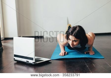 Home Training, Sport, Online Fitness Class. Young Fit Woman Doing Exercise On Mat Looking Video Guid