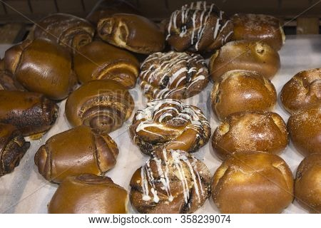 Many Fresh Buns With Sugar, Poppy Seeds, Cottage Cheese, Are On The Counter Of The Bakery Shop