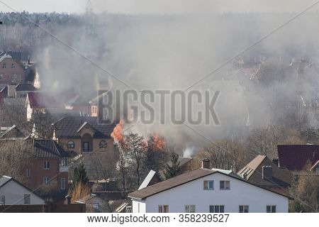 Smoke In A Residential Village Among Houses On Fire. Houses Against The Background Of Fire Bringing