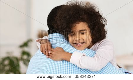 Family Bonding Concept. Adorable African American Girl Hugging Her Grandpa At Home