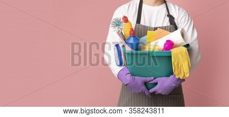 Bucket With Cleaning Supplies And Tools In Hands Of Unrecognizable Man In Apron Standing On Pink Bac