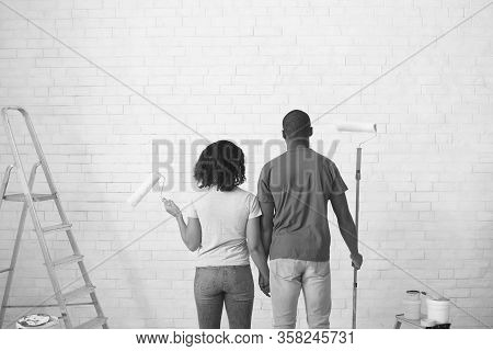 Homemade Repair. African American Couple With Rollers In Hands Black And White Photo, Back