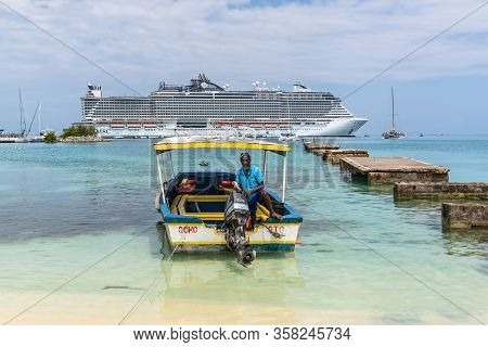 Ocho Rios, Jamaica - April 22, 2019: Boatman In A Wooden Motor Boat On The Background Of A Cruise Sh