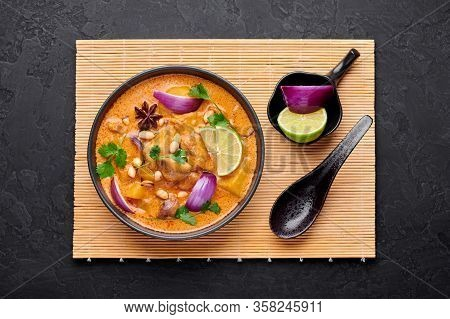 A Chicken Massaman Curry In Black Bowl At Dark Slate Background. Massaman Curry Is Thai Cuisine Dish