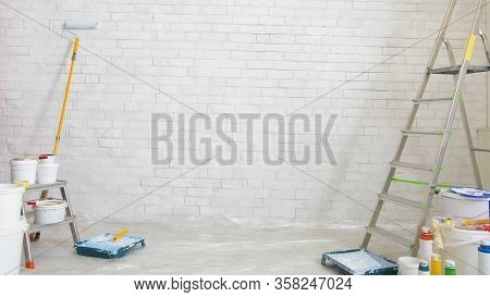 Ladder, Paint And Tools For Making Repair In Empty Room, White Bricks Wall, Panorama, Copy Space