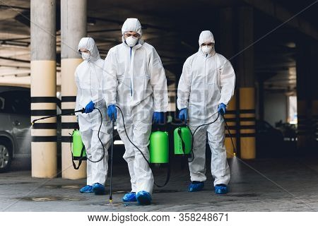 World Epidemic. Workers In Coronavirus Suits Cleaning Streets With Chemicals Disinfection, Copy Spac