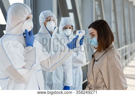 Coronavirus Risk. Medical Workers In Protective Suits Measuring Temperature Of A Woman Outdoor, Copy