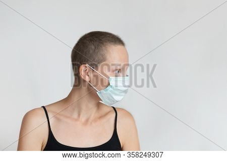 Profile Side View Of Short Haired Young Adult Woman Wearing Protective Facial Mask On Face Against W