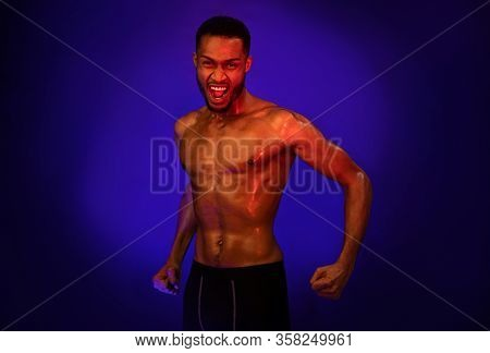 Aggressive Shirtless Black Fighter Guy Shouting Clenching Fists Ready To Fight Posing On Blue Backgr