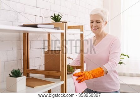Housekeeping And Cleaning Service Concept. Senior Woman Wiping Furniture At Home, Free Space