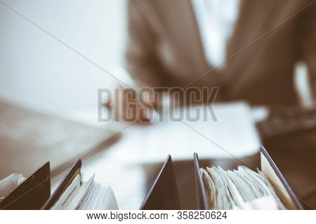 Binders Of Papers Waiting To Process By Bookkeeper Woman Or Financial Inspector, Close-up. Business