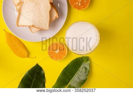 Breakfast Table With Sliced Bread And Glass Of Milk On Yellow Background, View From Above Table.