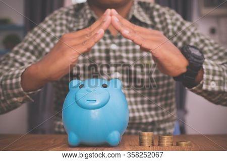 Businessman Holding Hand Home Sign On Piggy Bank.