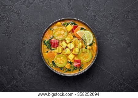 Yellow Veg Thai Curry With Tofu And Vegetables In Black Bowl At Dark Slate Background. Vegetarian Th