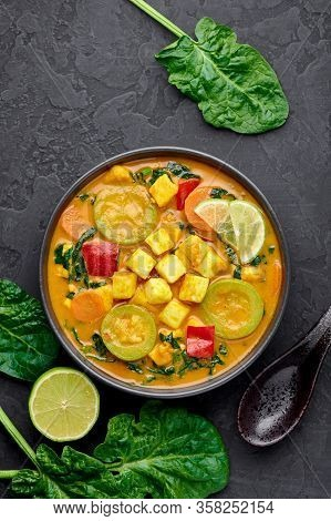A Yellow Veg Thai Curry With Tofu And Vegetables In Black Bowl At Dark Slate Background. Vegetarian
