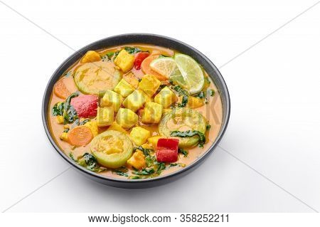A Yellow Veg Thai Curry With Tofu And Vegetables Isolated On White Background. Vegetarian Thai Curry