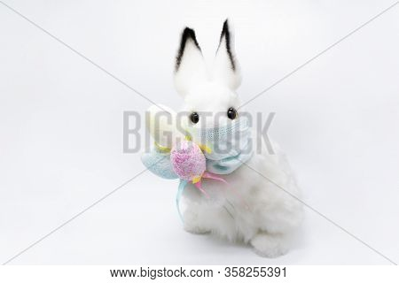 Easter Bunny In A Facial Medical Mask With A Bouquet Of Colorful Eggs. The Concept Of Easter And Qua