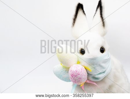 Close Up Of Easter Bunny In A Facial Medical Mask With A Bouquet Of Colorful Eggs. The Concept Of Ea