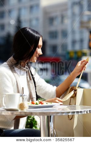 Image of happy female in open air cafe looking at paperbags in urban environment