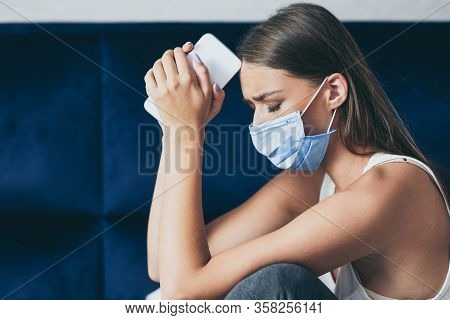 Self-quarantine Depression. Depressed Girl In Protective Mask Holding Phone Sitting In Bed During Co